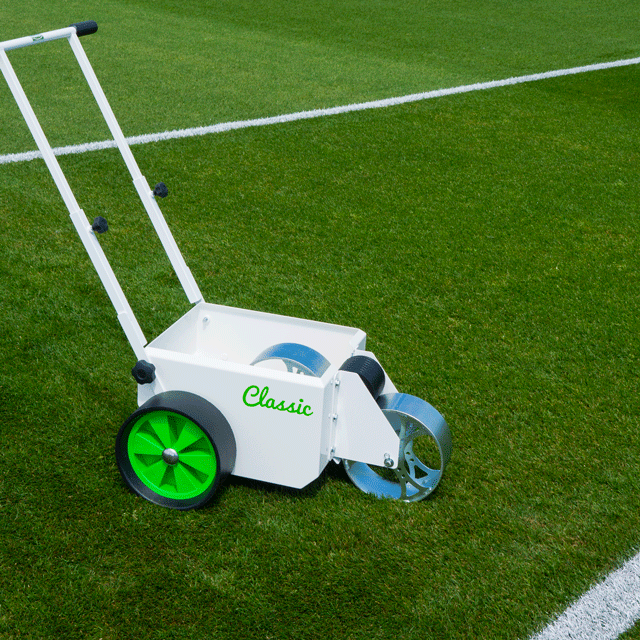 Image of a white, square bodied line marker, with two solid wheels at the back and a steel wheel at the front for transferring paint, located on a grass sports pitch.