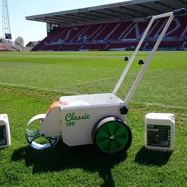 Image of a white, square bodied line marker, with two solid wheels at the back and a steel wheel at the front for transferring paint, located on the pitch at Swindon Town's pitch, along with 2 drums of Extreme line marking paint.