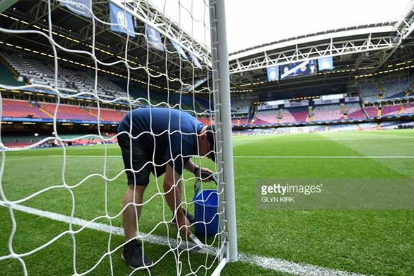 A groundsman applies the finishing touches to the pitch at the Principality Stadium in Cardiff.