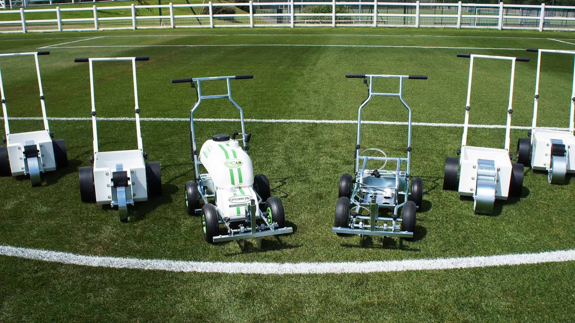 Photo of a range of white and metal line marking machines laid out on a grass sports pitch.