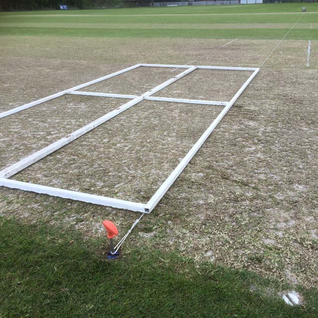Image of a cricket wicket, with an orange handled metal pin in the ground, and a white framework laid out across the crease.