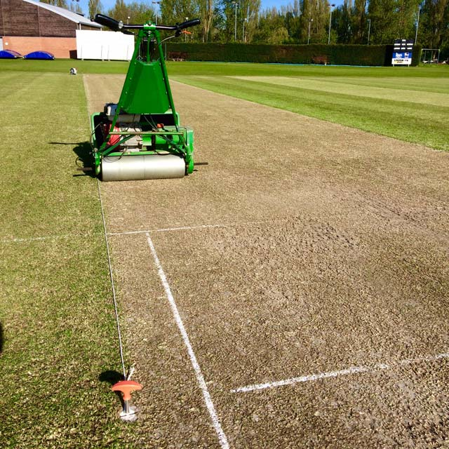 Image looking down a cricket wicket, with string laid out along the floor from an orange handled metal pin in the ground at one end, down to the other end.  A green mower sits on the wicket.