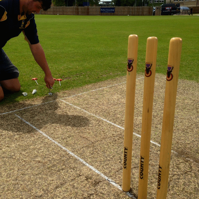Image of a groundsman kneeling down near the crease on a cricket wicket, using a metal tool to screw in a white plastic screw carrot.