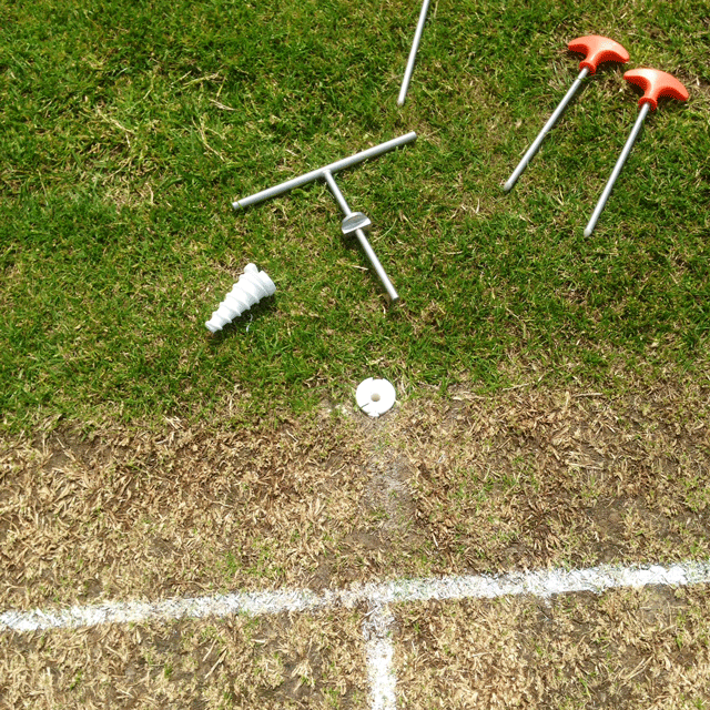 Close up birdseye view of a cricket wicket, with a metal key tool, metal pins and a white screw carrot laid out on the grass.