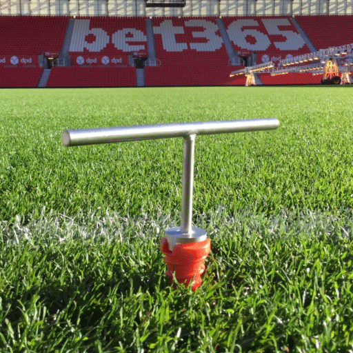 Close up of an orange plastic screw socket halfway in the ground, with a metal key tool attached, on the side of the pitch at Stoke's Britannia Stadium.