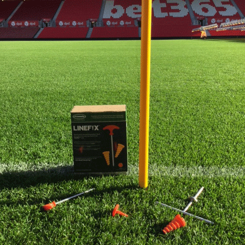 A one metre plastic yellow pole in the ground on the side of the pitch at Stoke's Britannia Stadium, with LineFix products lying around.
