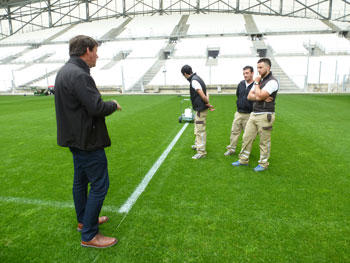 Photo of Pitchmark MD Mark Rodman speaking to grounds staff on the pitch in the Stade Velodrome, Marseille, France.