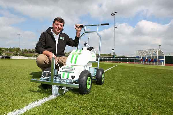 Pitchmark Managing Director Mark Rodman with an Eco Pro spray line marker on a grass football pitch.