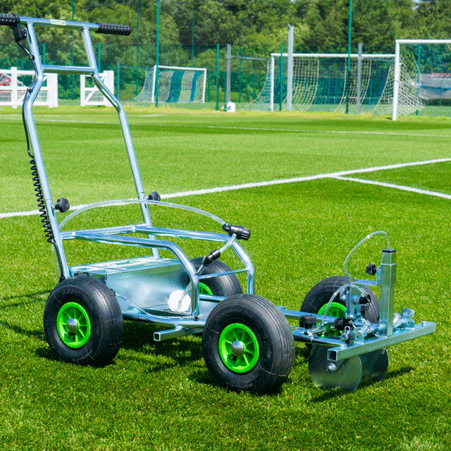 Image of a four-wheeled Eco Club spray line marker, with tubular metal chassis and handlebars, on a grass sports field.