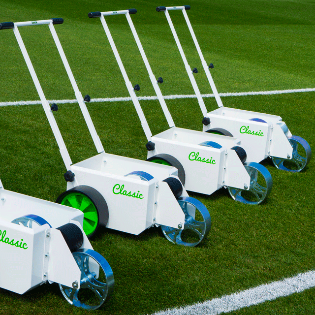 Image of four white, square bodied line markers, with two solid wheels at the back and different sized steel wheels at the front for transferring paint, located on a grass sports pitch.
