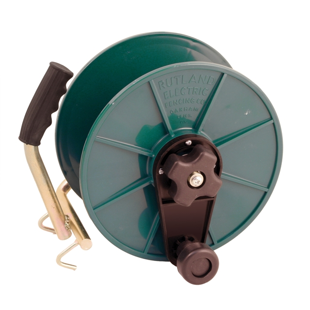 Image of a green plastic wind up reel, with brass handle and rubber hand grip.