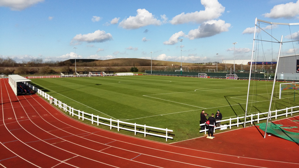 Wide angle photo of the first team football pitch at SGS college, with a running track round the outside.