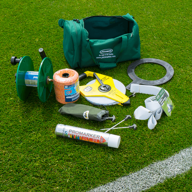 Image of products laid out on a grass sports pitch, including a green sports kit bag, white aerosol paint can, rubber circle, 10 metal pegs and large measuring tape.