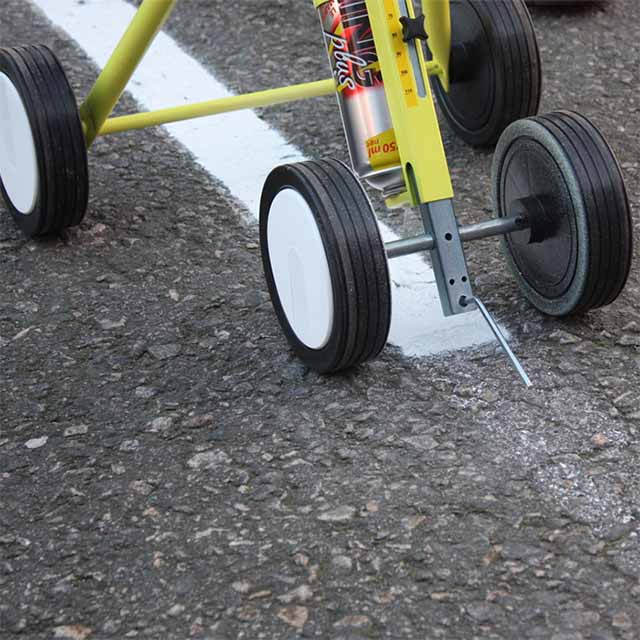Image of white line being marked out on a concrete surface with a yellow four-wheeled aerosol spray marking machine.