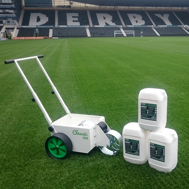 Image of a white, square bodied line marker, with two solid wheels at the back and a steel wheel at the front for transferring paint, located on the pitch at Derby County's Pride Park pitch, along with 3 drums of Direct line marking paint.